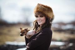 portrait of a beautiful smiling girl in a fur hat with little dog - stock photo