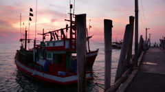 Thai fishing trawlers tied to pier with deep red sky and purple sea Stock Footage