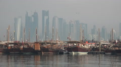 Qatar, Doha, dhow harbor, wooden vessels, modern skyline, Middle East Stock Footage