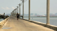 Young Asian teenager walks on fishing boat pier with seascape back ground Stock Footage