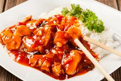 Sweet and sour chicken with rice on a plate - stock photo