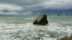 New Zealand Catlins surf churns around tooth shaped rock Stock Footage
