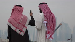 Doha, Qatar, two Saudi men take pictures of skyline and port Stock Footage
