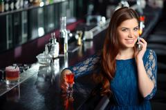 Young woman uses her phone in the bar - stock photo