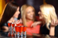 Three women have a drink in the bar - stock photo