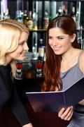 Two friends examine menu - stock photo