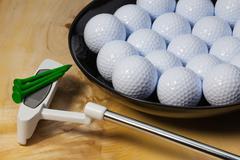 Black ceramic bowl full of golf balls and putter - stock photo