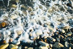 Wave of the ocean sea on the cobble beach at the sunset light. Close up view. Stock Photos
