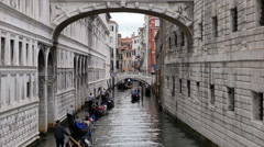 Gondola traffic under Bridge of Sighs on narrow side canal in Venice, Italy Stock Footage