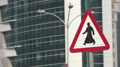 Doha, Qatar, road sign, pedestrian crossing, traditional dress, Middle East Stock Footage