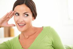 Stock Photo of Beautiful woman with toothy smile looking away and smiling with confidence at