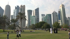 Families visit public park with Doha skyline Qatar, leisure in Middle East Stock Footage