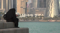 Veiled Arabian woman uses smartphone in front of modern Doha skyline Stock Footage
