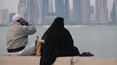 Doha, Qatar, a Muslim couple watch over city's skyline, mobile phone Stock Footage