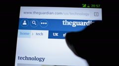 Surfing the guardian worldwide newspaper website on mobile phone touch display - stock footage