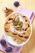 Freshly baked plum cake in a casserole dish - stock photo