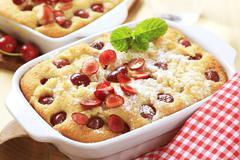 Freshly baked cherry sponge cake in a porcelain casserole dish - stock photo