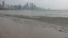 Doha, Qatar, defocused skyline, waves at beach Stock Footage