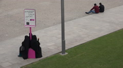 Doha, Qatar, three women in burqa at a shuttle bus stop Stock Footage
