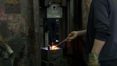 Smith in smithy holding hot metal on anvil and big mechanical hammer punching. Stock Footage
