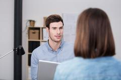 Serious Office Man Talking to Woman at his Office Stock Photos