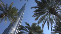 Dubai, Burj Khalifa tower, palm trees, blue skies, tourism - stock footage