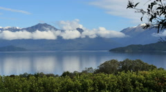 New Zealand Lake Manapouri mountains with cloud collar pan Stock Footage