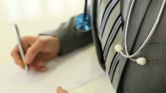 Doctor's hand writing prescription Stock Footage