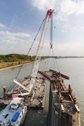 Floating crane carrying girder platform to support a bridge deconstruction on - stock photo