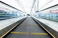 Symmetric moving blue escalator inside contemporary airport Stock Photos