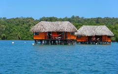 Overwater bungalow with thatched roof - stock photo