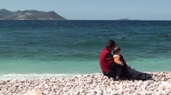 Mother and son sitting at the sea brim 2 - stock footage