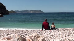 Mother and son sitting at the sea brim - stock footage