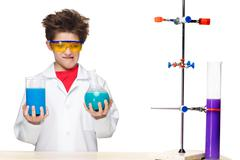 Little boy as chemist doing experiment with chemical fluid in the laboratory Stock Photos