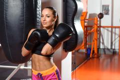 Female boxer with punching bag - stock photo