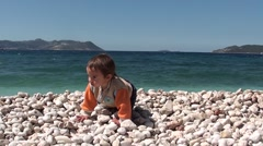Toddler on pebbles crawls stands up and walks Stock Footage