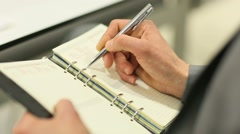 Closeup of businessman writing on agenda Stock Footage