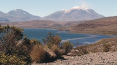 View to the Chungara lake with volcanic mountain range at the background, Chile. Stock Footage