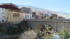 Bridge over mountain river by a village sitting on a high riverbank Stock Footage
