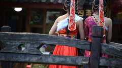 Two women in Nahsi traditional costume at the bridge in Lijiang Stock Footage