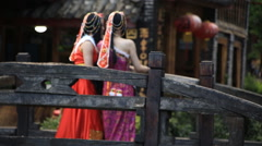 Two woman in Nahsi traditional costume at the bridge in Lijiang Stock Footage
