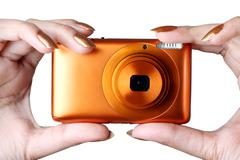 Female taking photo with a digital compact camera Stock Photos