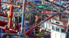 Colorful Thai fish trawler with crewman hosing deck Stock Footage