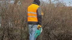 Landscape worker with bush cutter near bush in spring Stock Footage