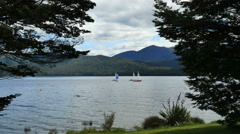 New Zealand Lake Te Anau sailboats in front of hills Stock Footage