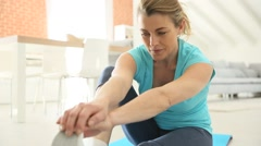 Mature woman at home doing stretching exercises Stock Footage