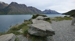 New Zealand Lake Wakatipu flat boulder near shore viewpoint Stock Footage