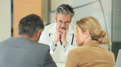 Doctor meeting couple in doctor's office Stock Footage