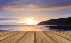 sunrise over incoming tide with rocky foreground and cliffs with wooden plank - stock photo
