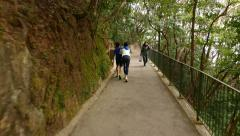 Walking up the hill pathway, following two boys Stock Footage